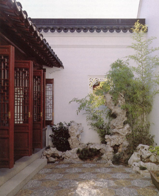 Fantastically shaped Taihu rocks are sculptures in a courtyard of polished pebbles laid in an intricate pattern