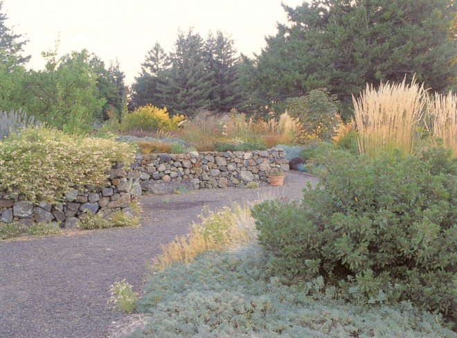 Walls built of native stone provide a strong unifying structure for beds of grasses, perennials, and shrubs