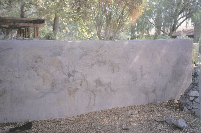 A straw bale wall provides spatial definition, a handsome backdrop for plants and creativity in the application of simulated petroglyphs on its finished surface. (The Arboretum of Los Angeles County)
