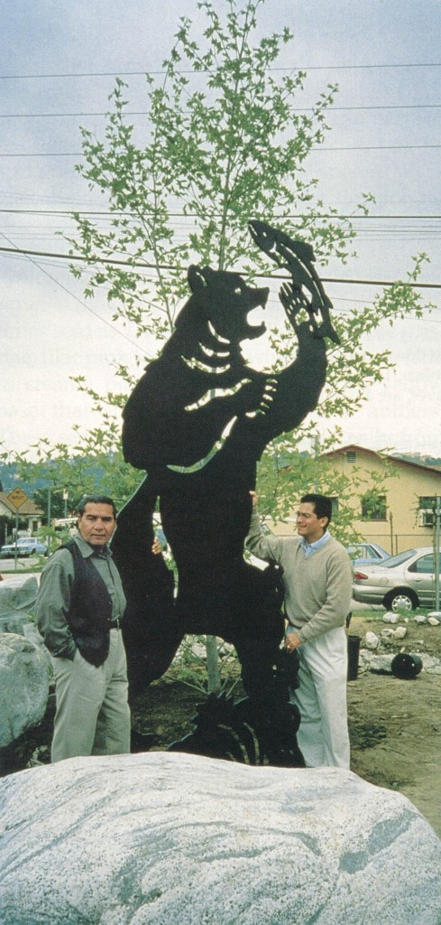 At Osos Park, artist Michael Amegua and Congressman Xavier Becerra pose beside a cut-out sculpture of a grizzly, once a resident of the Los Angeles River area