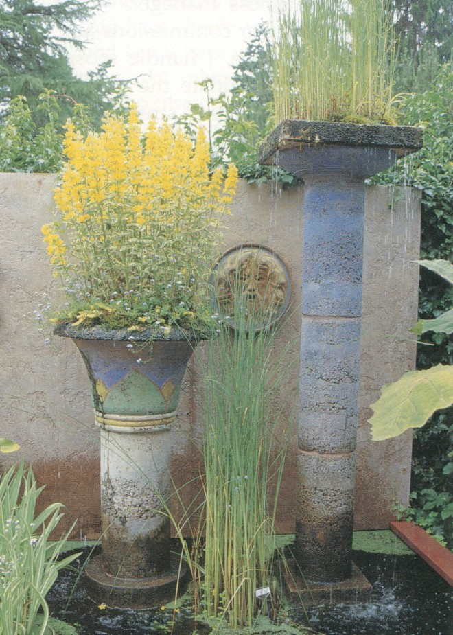 Fountain columns highlight one end of the entry pool. Lysimachia alexander tops the Egyptian column, while dwarf cattail (Typha minima) extends the height of the Doric column. Our interpretation of the Bocca di Veritas in Rome was created using a friend as a model. Behind it all is a fake stucco wall.