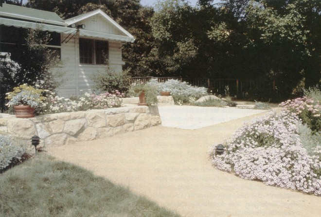 The Home Demonstration Garden featuring a blue grama (Bouteloua gracilis) lawn, sandstone seatwalls, decomposed granite paths, and perennial borders with seaside daisy (Erigeron glaucus) in the foreground