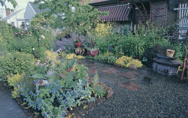 A gravel and stone terrace, surrounded by a riot of color and texture, fills the space vacated by the front lawn in Nancy Goldman's Portland garden