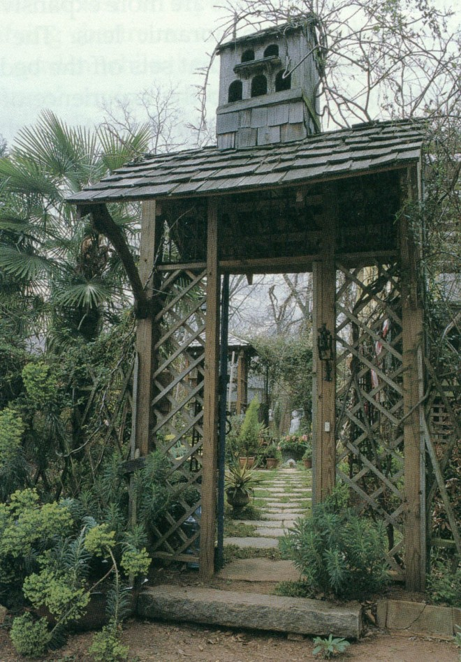 An elaborate streetside gateway, topped by a dovecote, opens to a view of the private garden at the Garcia residence. Photograph by Coleston Burrell