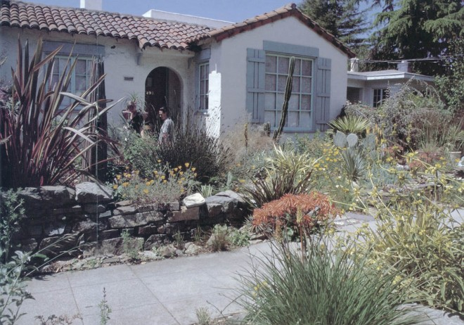 A low, dry-laid stone wall provides a sense of enclosure for the front garden, yet leaves the plantings open for enjoyment by passersby. A tall wooden sculptural element on the left repeats some of the strong lines of New Zealand flax (Phormium), red hot pokers (Kniphofia), a restio (Chondropetalum), and a single columnar cactus (Cereus peruvianus). California poppies (Eschscholzia californica), various aloes, and Phlomis aurea provide springtime flowers in oranges and golds. Photograph by RGT