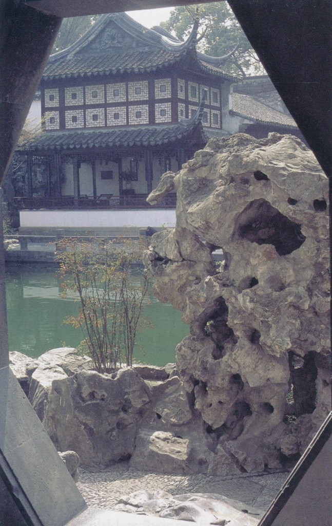 A diamond-shaped door leads to a view of an elaborate pavilion beyond a large pond, with an eroded rock and a single plant of Nandina domestica in the foreground. Author's photographs