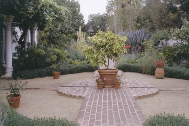A remnant of the original brick pathway passes through the mediterranean garden that fills the space between the pergola (on the left) and the wall at the property line (on the right); the rill crosses through the brick path, connecting the fountain on the house with a new fountain on the perimeter wall
