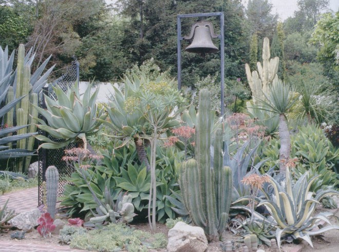 A Mission bell accents the succulent garden; the Moorish gates are barely visible on  the left