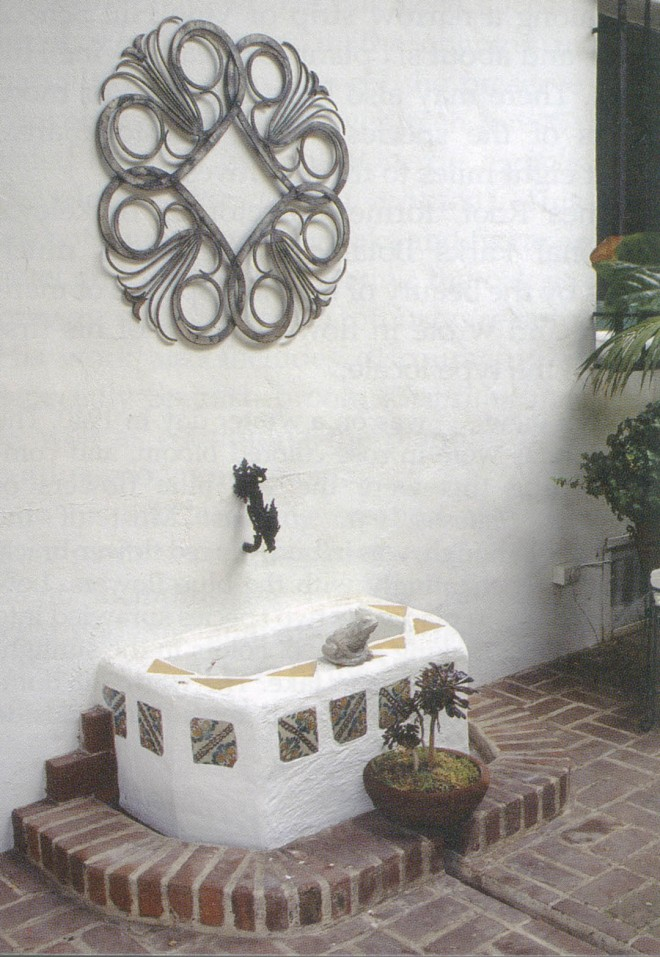 A simple Moorish stucco and tile fountain is the source of water for a rill that runs through the brick pavement
