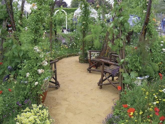 A hazel wood and grape vine gazebo shelters a sitting area of distinctive hazel chairs; all were crafted by Baz Scampian. Roses, meadowfoam (Limnanthes douglasii), and Shirley poppies (Papaver rhoeas) flank the entrance to the sitting area