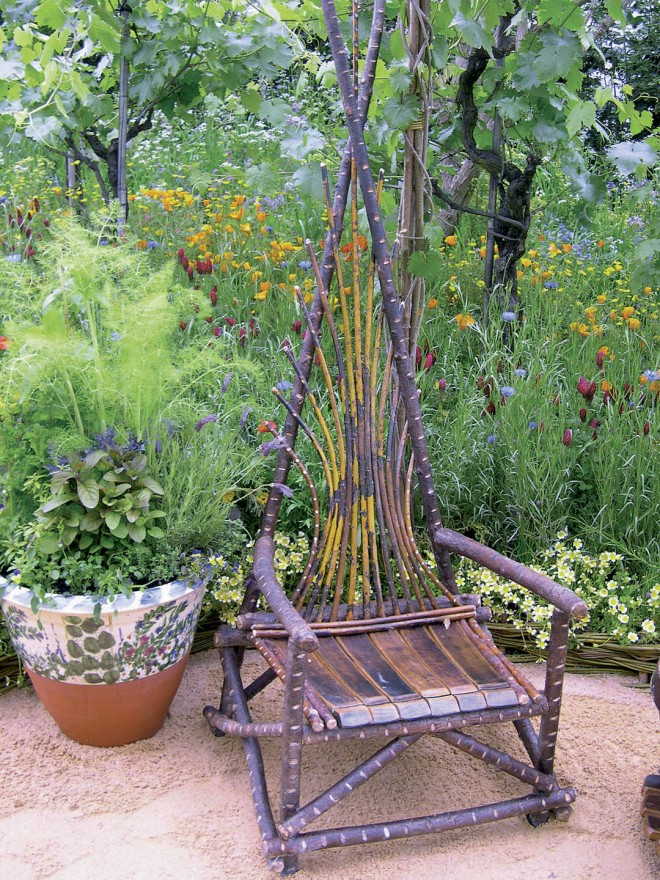 Wildflowers and mature grape vines provide the backdrop for the hazel chair and a painted terra cotta container of herbs, reminiscent of those at the Fetzer Winery