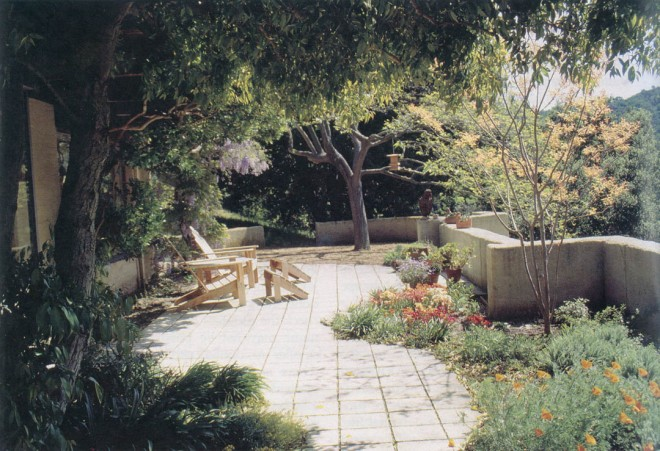 Author's former garden in Martinez, California with pavement and rammed earth walls providing fire protection close to the house; plantings are low water-using species that will add little to a fire
