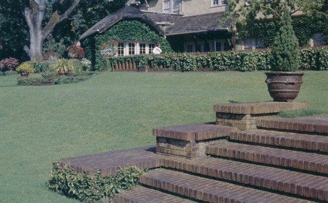 Carefully detailed brick steps mark a slope in the lawn below the brick terrace