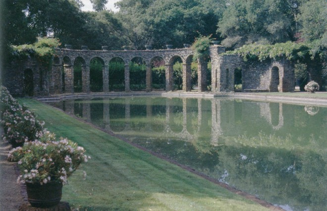 The aqueduct-like stone arcade reflected in the still water of the Roman Pool; glazed ceramic urns sit atop the columns and match along the edges of the pool