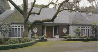 The O'Malley home in Woodside, California under a valley oak (Quercus lobata); tall specimens of Camellia japonica 'CM Wilson' flank the main windows. Photograph by RGT