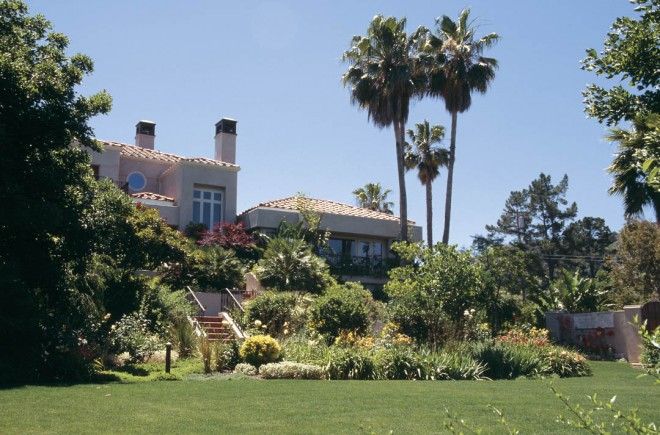 The contemporary Mediterranean-style home sits on the highest point of the property; the lawn below was trimmed to the size needed to accommodate a large gathering. On the left, a mature naked coral tree (Erythrina coralloides) separates the lawn from the pool terrace. Photographs by RGT, except as noted