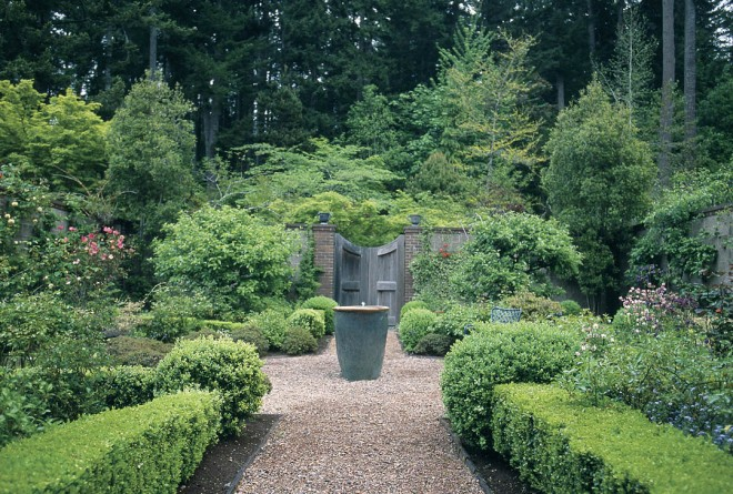 A garden within a garden is revealed upon entering Anne's secluded, European-inspired walled sanctuary. The formally designed landscape is made more alluring when viewed in contrast to the natural woodland outside its walls. Water bubbles in a classic urn, placed on crushed stone at the axis of the garden's formal quadrants.