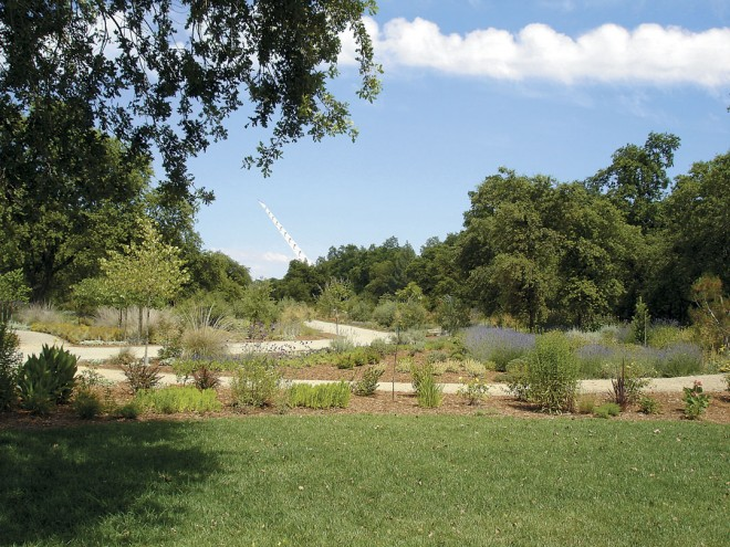 View down the length of the display garden walk at McConnell Arboretum & Gardens, with the  Sundial Bridge in  the distance