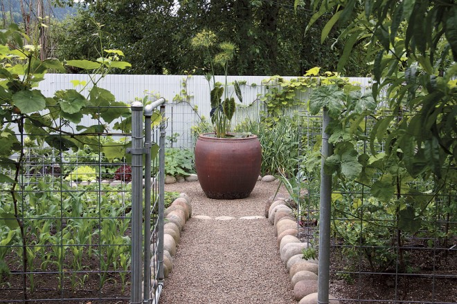 Rounded boulders edge the beds in the vegetable garden, where a second water garden holds center court in a glazed Vietnamese urn