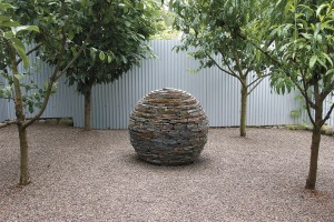 The austere character of the fruit orchard contrasts with the rest of the horticulturally rich garden; the stone sphere was built by the owners