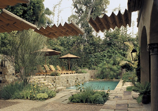 Shade from umbrellas and overhead canopies, broad paved areas, comfortable seating, screening from the neighbors, and a small swimming pool make for a livable Santa Monica garden by landscape architect Laurie Lewis. Photograph by David Phelps