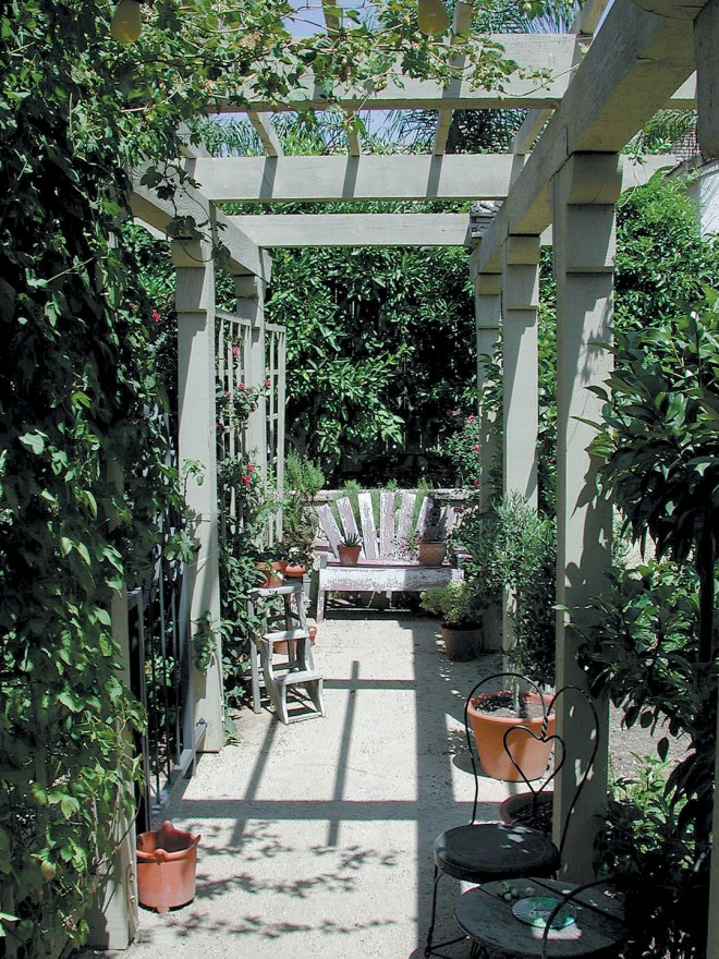 Terracotta pots and garden furniture take advantage of the shade produced by the arbor