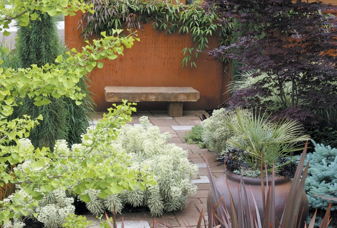 A simple sandstone bench sits against a six-foot-tall rusty steel screen that separates the Gregory garden from the too-close neighbors