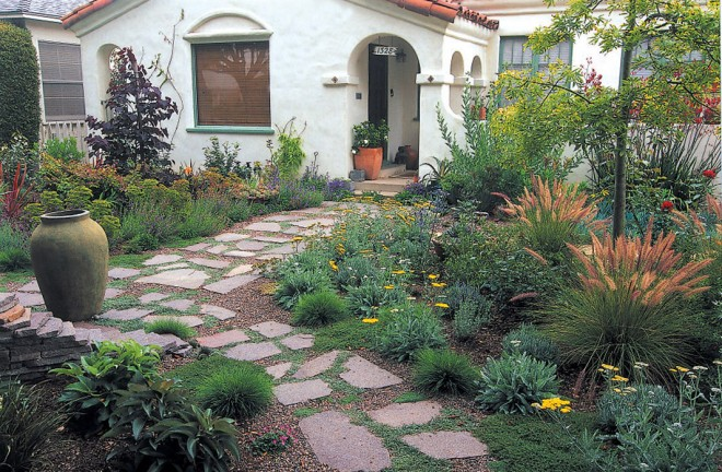 A wide flagstone path leads through a colorful garden of low, flowering plants to the front door; containers hold succulents near the house and a camellia on the porch