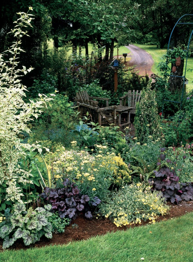A sitting area for two nestled into a bower of hydrangeas and other shade-loving shrubs and perennials