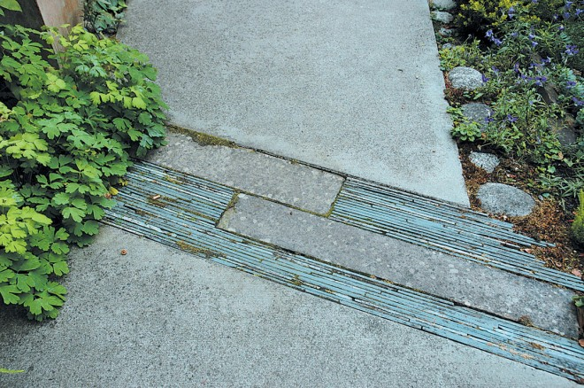 Slate, recycled from the dismantled sunroom and set on edge, relieves the expanse of concrete pavement