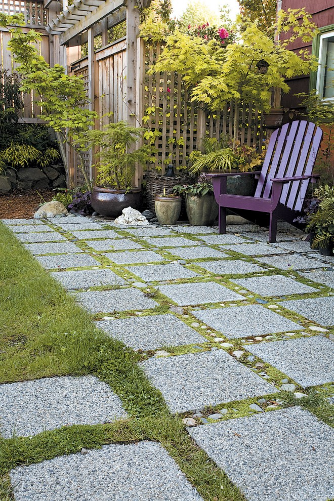 Behind the house, Jennifer jackhammered out the old concrete slab and replaced it with a permeable patio of pavers interspersed with ribbons of stone