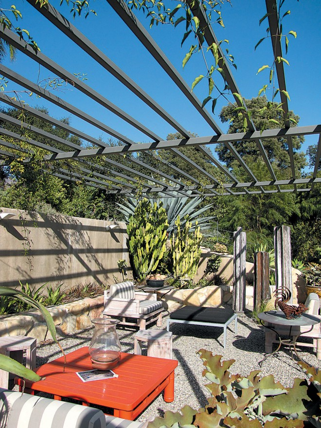 The new garden room, roofed by a steel arbor rapidly being covered by flame vines (Pyrostegia venusta); a pale columnar euphorbia fills one corner; sculpture and found items abound. Photograph by RGT - See more at: http://www.pacifichorticulture.org/articles/the-sustaining-garden/#sthash.mpiIYUdx.dpuf