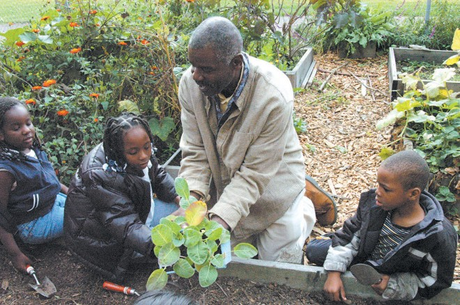An OBUGS volunteer teaches students about planting vegetables