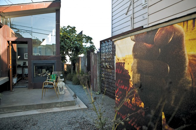 View from the gate to the studio and side yard; the fist billboard panel hides the bike storage shed; an indoor outdoor fireplace heats the sitting room and the outdoor terrace