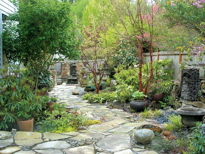 A beautifully laid stone path, combined with stone containers and salvaged architectural details in a garden designed by Phil Wood; Jim DuBois was the stonemason
