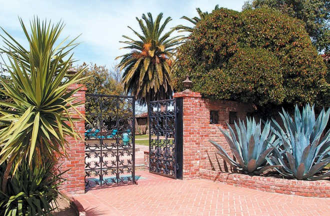 Yucca and agave stand guard either side of of the cast-iron courtyard gates, salvaged from a San Francisco bank