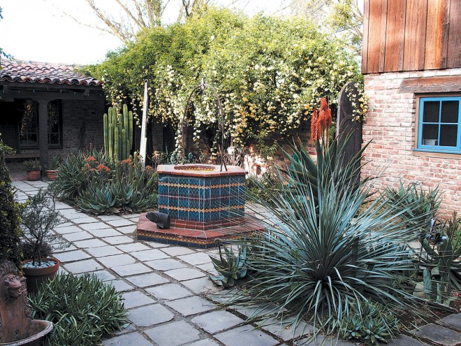 Cacti and succulents surround a tiled well in the courtyard of the former guesthouse