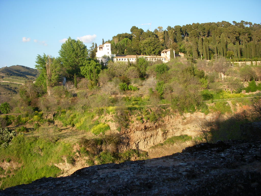 The native landscape outside the Alhambra remains naturally dry in contrast to the lush plantings within.