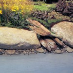 """A Pacific Northwest Beach Garden"" Created by: Plantswoman Design, Inc. and The Reijnen Company  The artful use of boulders and driftwood evoke the shores of Puget Sound while generous drifts of drought-tolerant coastal plants create a hardy and resilient, low-maintenance landscape."