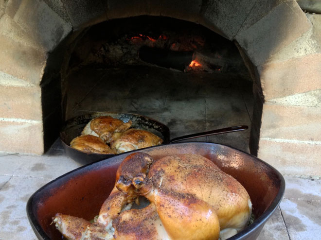 Succulent roast chicken just emerging from the wood-fired oven. Photo: Warwick Hubber