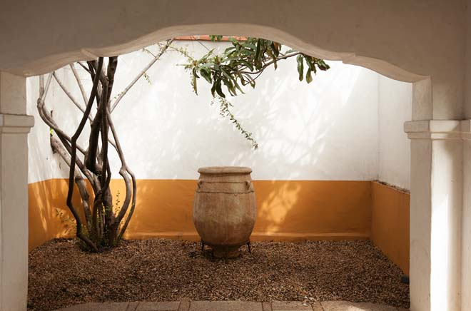 Shadow and light animate a living tableau featuring a large clay vessel off the porte-cochere. Photo: Jeff Dunas.