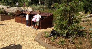 Kids explore the compost bins in Nature Garden's Get Dirty zone. Photo: Carol Bornstein
