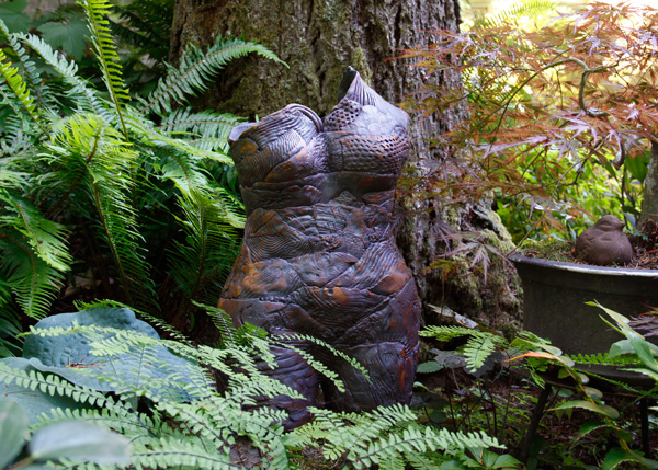 Earth Mother, stoneware, by Marilyn Woods, is appropriately sited among maidenhair ferns on a shady patio. Photo: Sharon Andrews