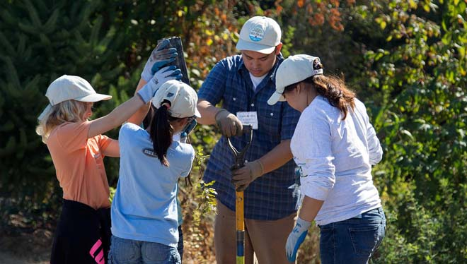 AmeriCorps member, Chase Huntley, works alongside elementary school volunteers at the Tree for All planting event at the Tualatin River Farm in Hillsboro, Oregon, kicking off the 1 Million–1 Year–1 Water campaign.  Photo: courtesy of Clean Water Services