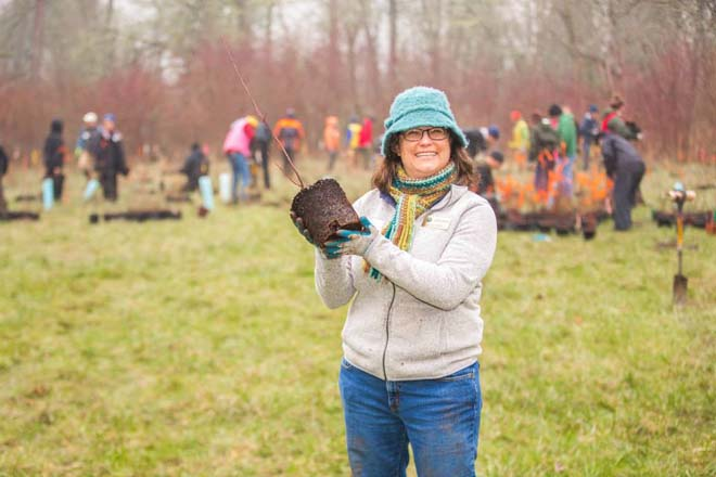 Despite the dreary winter weather, author Jennifer Nelson happily participates in a Tree for All planting event at Durham City Park.  