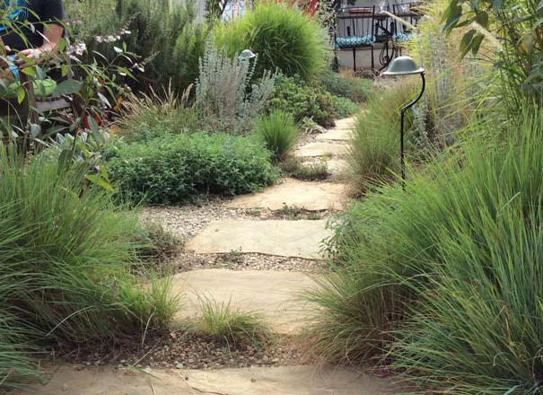 Stone stepping stones meander through grasses and resilient, water-wise perennials set in permeable gravel. Photo: Marilee Kehlmann