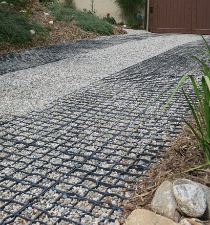 Permeable gravel surfaces finished with StabiliGrid tiles hold gravel in place and provide ADA-compliant wheelchair accessibility for the driveway and garden. Photo: Cordelia Donnelly