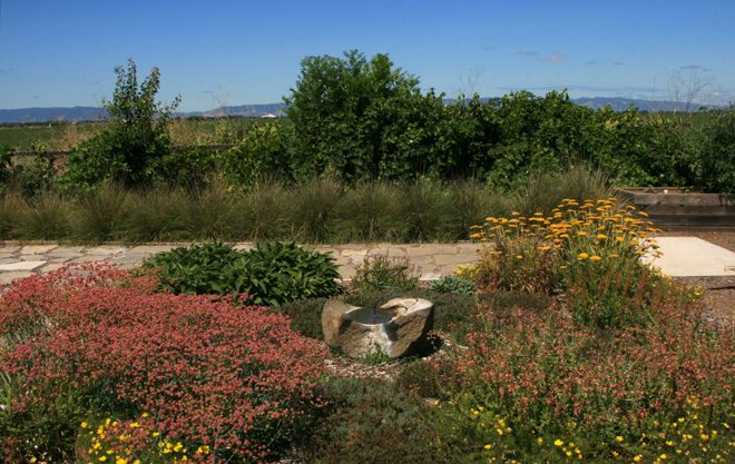 The pollinator garden, which looks out over agricultural fields against the western horizon, features a bird shower/bath and a permeable urbanite flagstone pathway. Photo: Jennifer Jewell