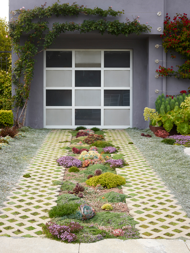 The checkerboard pattern on the garage door plays off the shape of the creeping mint-filled pavers. Next to the front door is bougainvillea under planted with Senecio vitalis 'Serpents' and aeonium in bloom. Photo: Marion Brenner