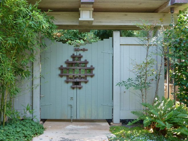 The entry courtyard is furnished with architectural detail and a handcrafted gate. Photo: Julie Monson